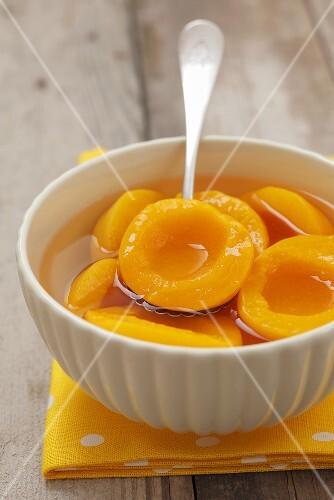A bowl of tinned peach halves