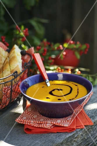 Cream of pumpkin soup with a baguette and pumpkin seed oil
