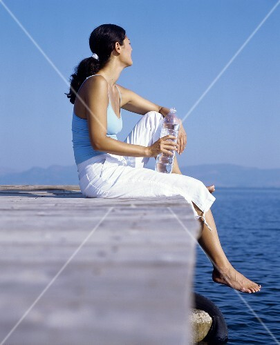 Young woman sitting on a landing stage