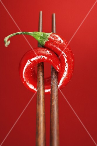 A chilli on chopsticks, red background