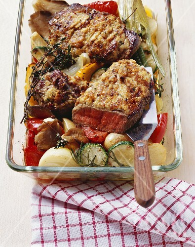 Fried entrecôte steaks with onion crust on roasted vegetables
