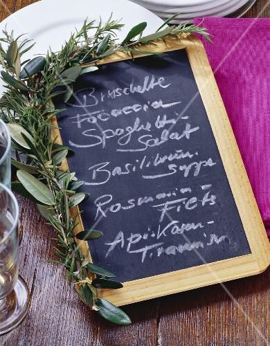 Menu written on slate board with herb decoration