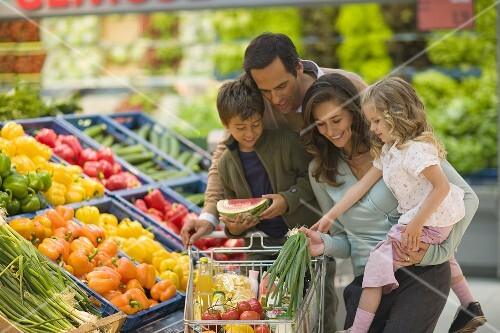 Family at the vegetable counter in a supermarket