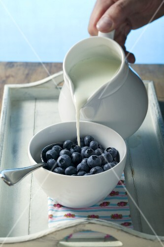 Pouring milk into a bowl of blueberries