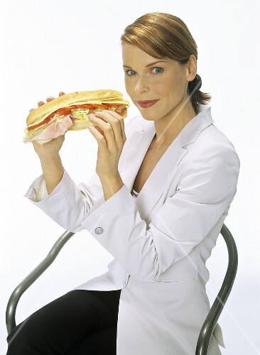 Young woman holding a sandwich in her hands