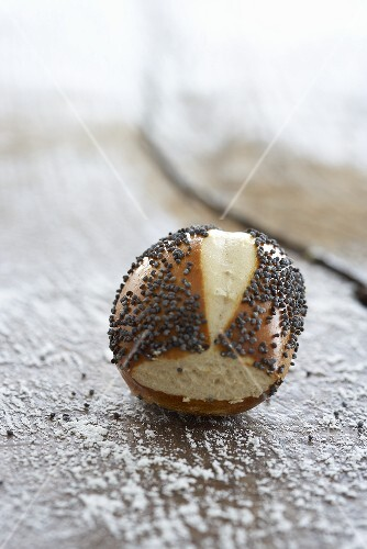 A lye bread roll with poppyseeds on a wooden surface