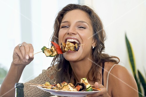 Young woman biting into grilled vegetable kebab