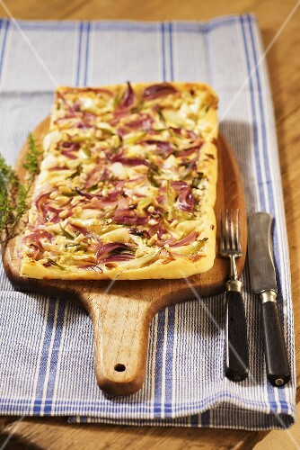 Zwiebelkuchen (onion cake) on a chopping board