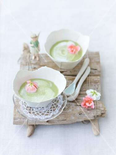 Two bowls of sorrel soup with geranium flowers on wooden board
