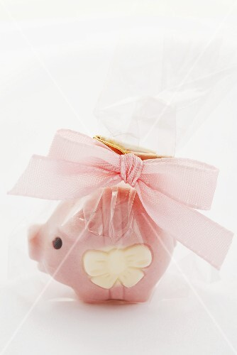 A lucky pink pig wrapped in cellophane and tied with a bow