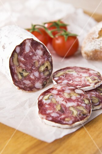 Walnut salami on paper with tomatoes and bread