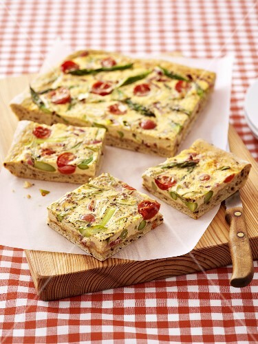 Tomato and asparagus quiche on a chopping board