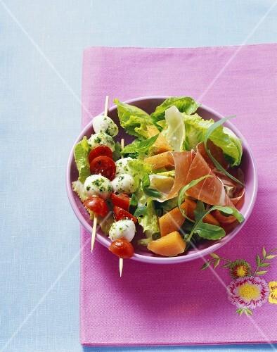 Tomato and mozzarella skewers on green salad, ham, melon