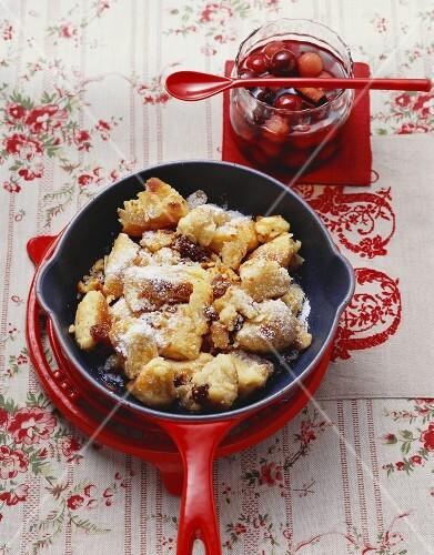 Semolina schmarren (pancake pieces) in frying pan, cherry compote in jar