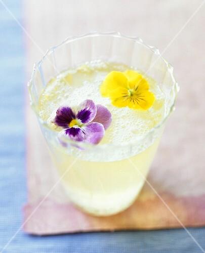 Champagner-Cocktail mit Zitrone und Essblüten