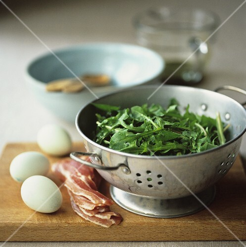 Dandelion leaves in a colander with bacon and eggs