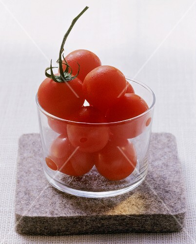 Several tomatoes in a glass