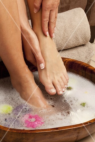 Feet in a foot bath with flower petals