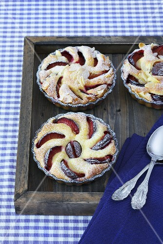 Plum tartlets in glass bowls on a wooden tray