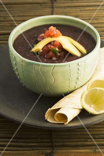 Black bean soup with avocado and tomato salsa and a tortilla
