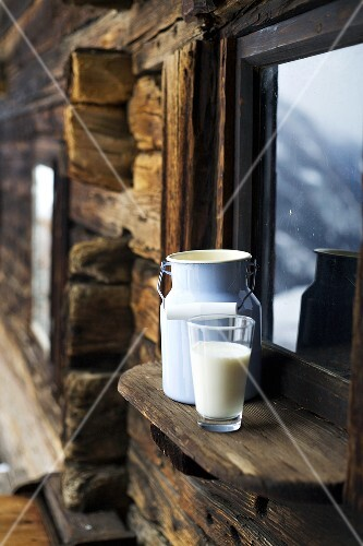 Milk can & glass of milk on window sill of Alpine chalet
