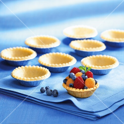 Shortcrust pastry cases, one filled with berries