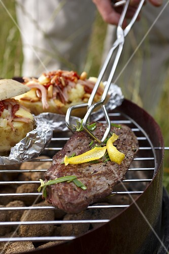 Beefsteak and baked potatoes on a barbecue