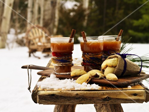 Hot Kentucky Toddies and biscuits on table in snowy garden