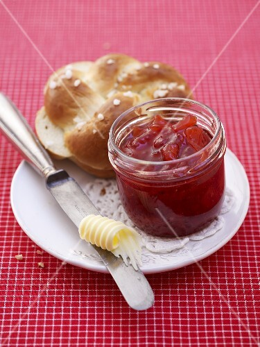 Strawberry and pineapple jam, butter and bread roll