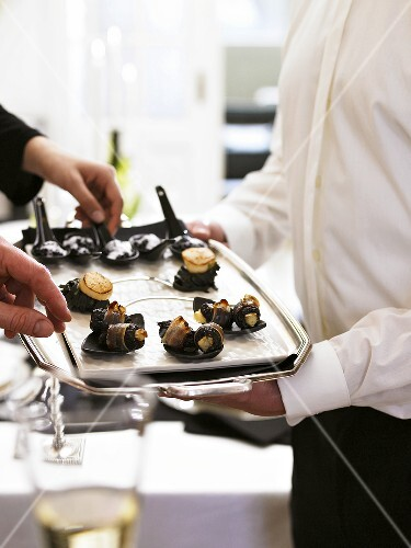 Waiter serving tray of bacon-wrapped prunes at champagne reception
