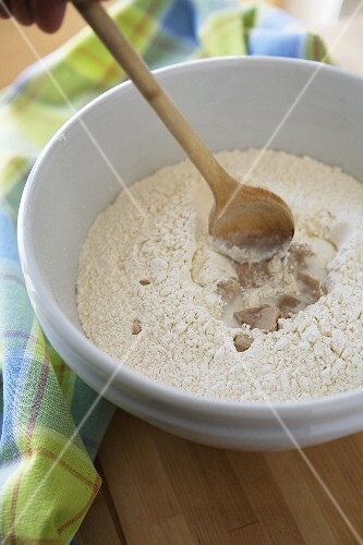Flour with yeast and milk in a bowl