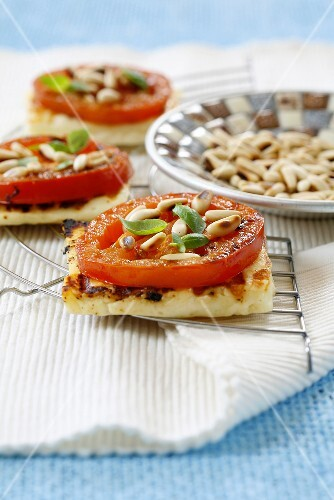 Grilled halloumi cheese with tomato and pine nuts