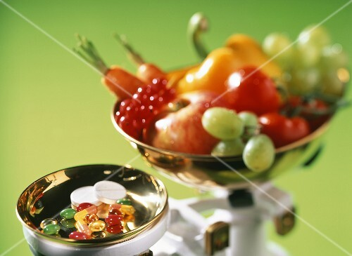 Pills and fresh fruit and vegetables