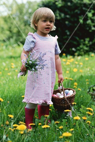 A little girl holding flowers and a basket of Easter eggs
