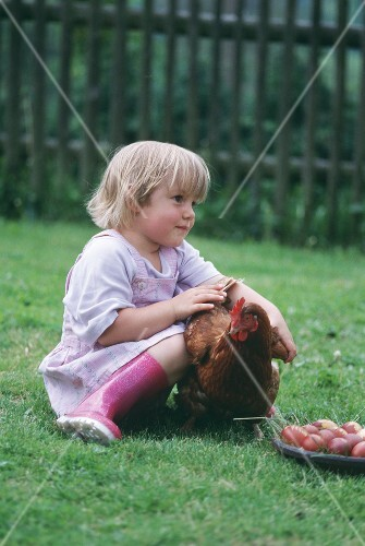 A little girl sitting on the grass with a chicken