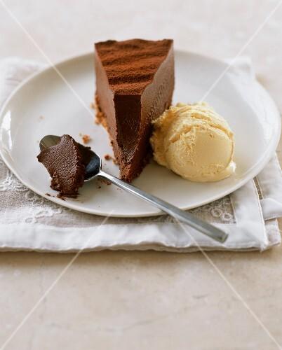 A slice of chocolate truffle cake with vanilla ice cream