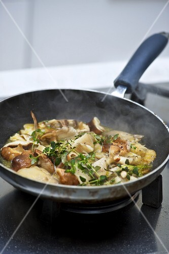 Mushrooms being fried in a pan