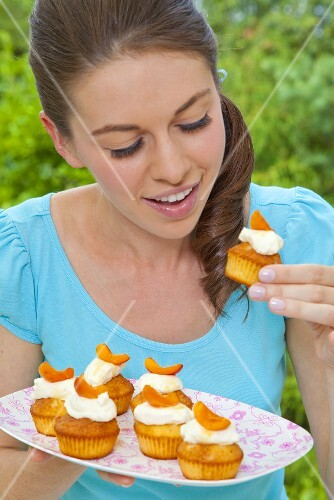 A young woman eating an apricot muffin