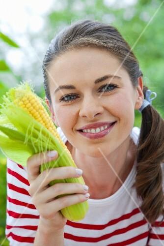 A girl holding a corn cob