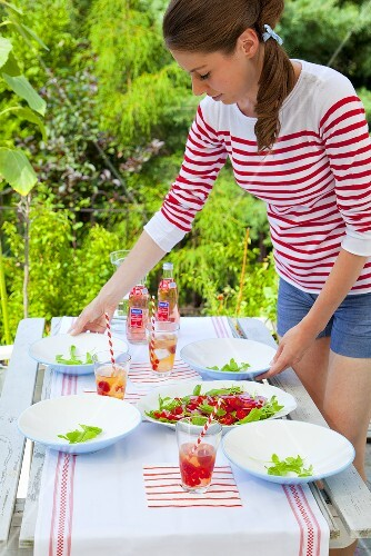 A girl serving a tomato and rocket salad in the open air