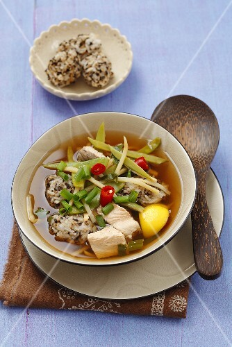 Broth with salmon, rice balls, bamboo and vegetables
