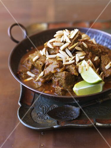 Beef curry with slivered almonds and lime wedges