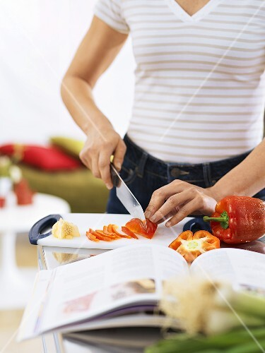 Woman slicing red pepper in kitchen