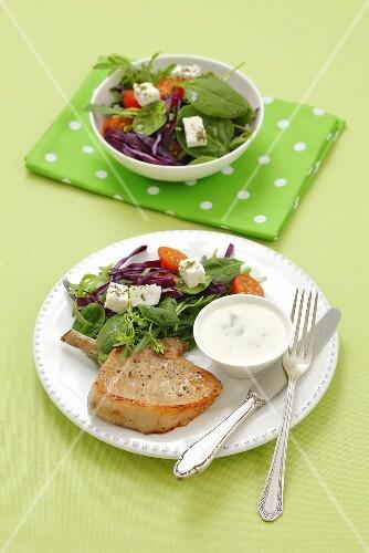 A pork chop with a vegetable salad, feta cheese and a yogurt dip
