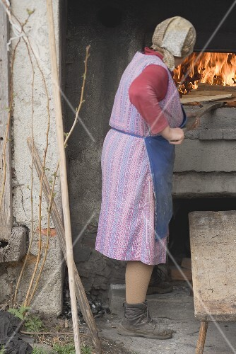 Countrywoman baking bread in stone oven