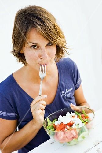 Young woman eating feta salad