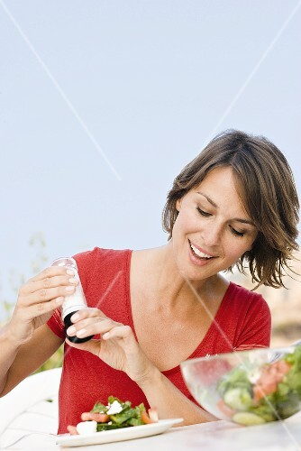 Young woman seasoning her salad out of doors
