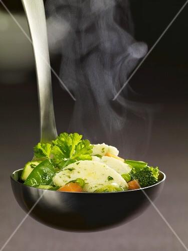 Ladle full of vegetable stew and semolina dumpling
