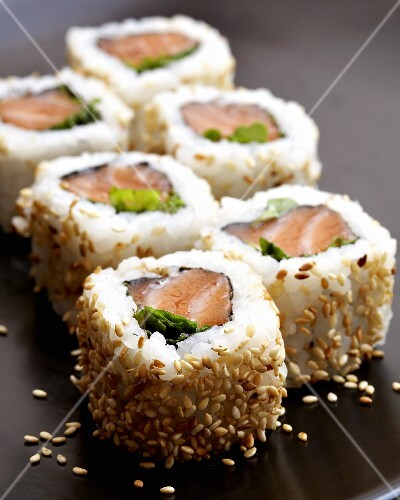 Six California rolls with salmon and sesame seeds