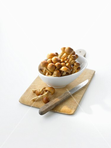 Nameko mushrooms in bowl on chopping board